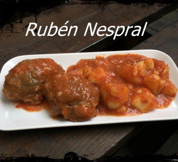 Carrilleras en salsa con pimientos rojos y guarnición de patatas.